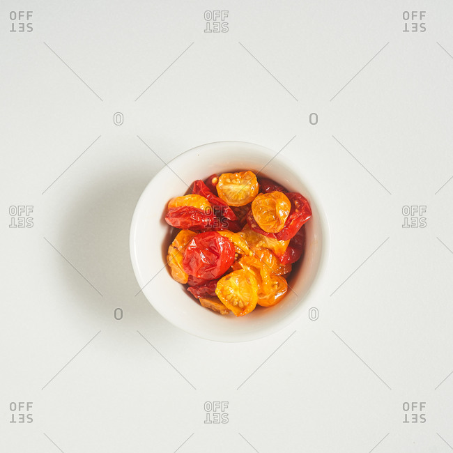 Red and yellow tomatoes in a small bowl on white background
