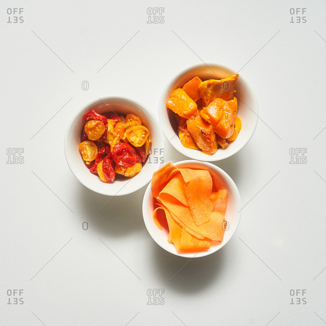 Tomatoes, carrots and butternut squash in small bowls on white background