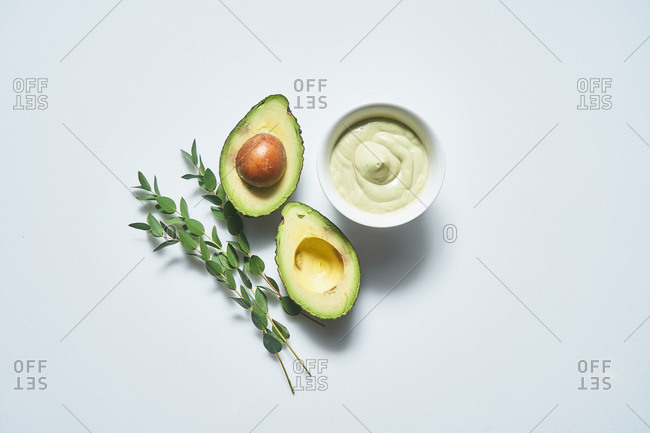 Overhead view of an avocado sauce in a bowl beside an avocado