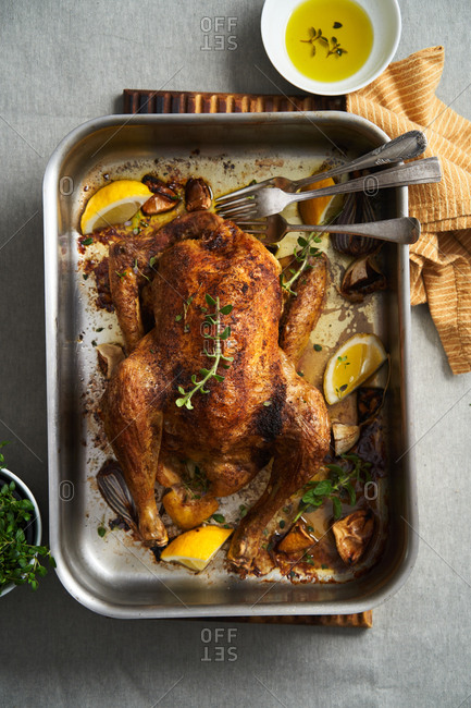 Whole roasted chicken in a roasting pan with lemon