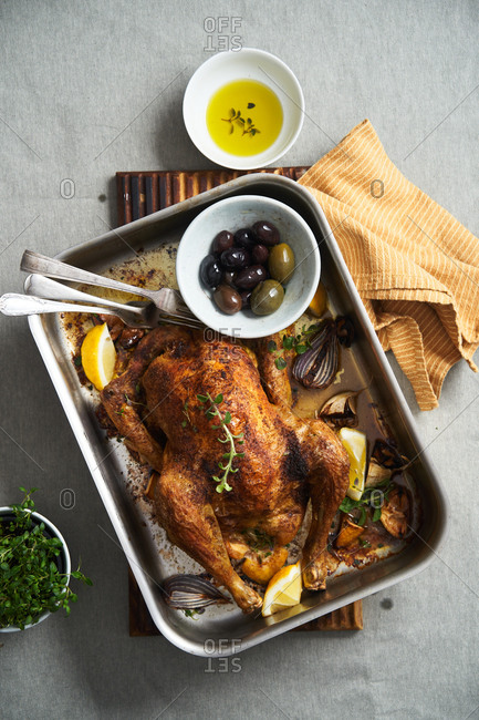Whole roasted chicken in a roasting pan with lemon and olives on table by salad