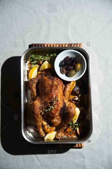 Whole roasted chicken in a roasting pan with lemon and olives