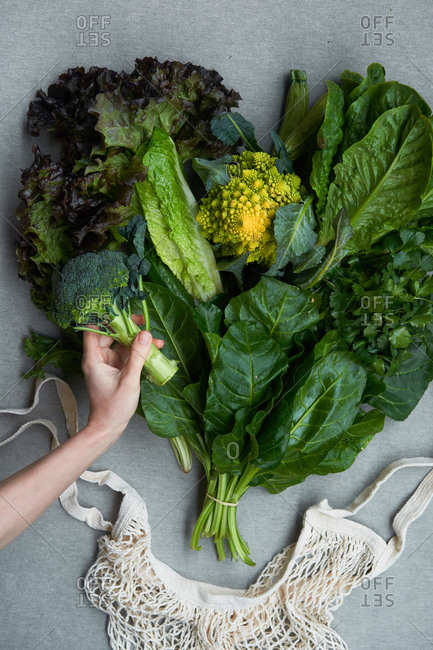 Woman's hand packing fresh produce with mesh sack on gray background