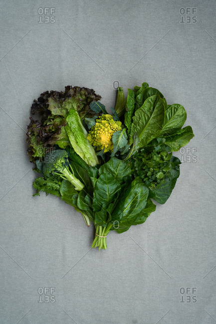 Heart shaped bunch of lettuce leaves and broccoli on gray background