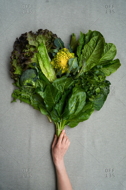 Woman holding a heart shaped bunch of leaves and broccoli on gray background