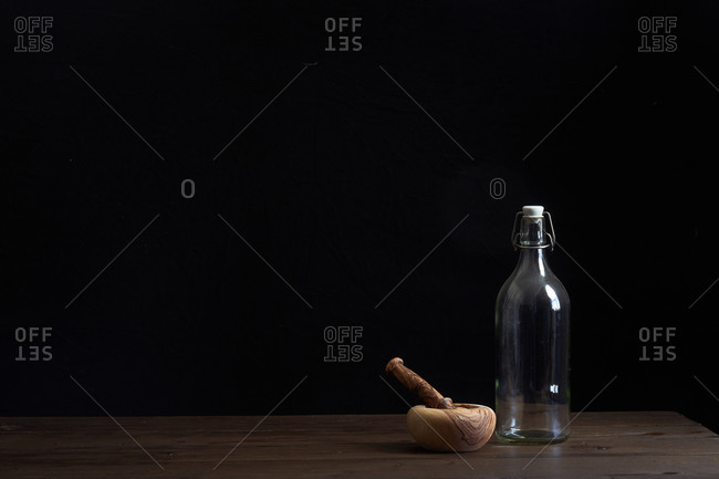 Glass bottle on wooden table beside mortar and pestle