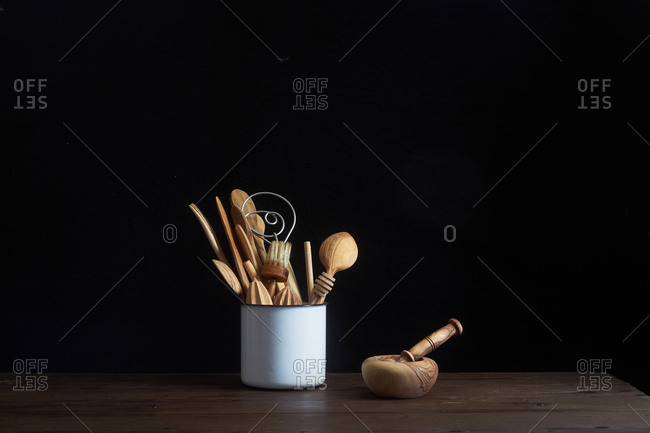 Container filled with wooden utensils on a table beside mortar and pestle
