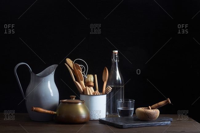 Container filled with wooden utensils on a table beside mortar and pestle, pitcher, water bottle and kettle