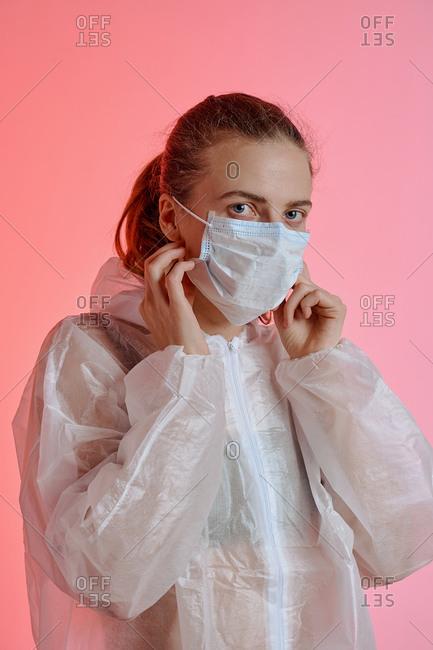 Woman adjusting medical mask and looking at camera