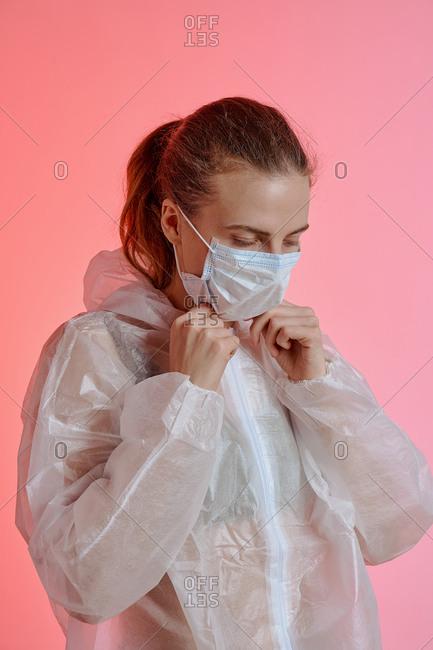 Woman protective coveralls adjusting medical mask