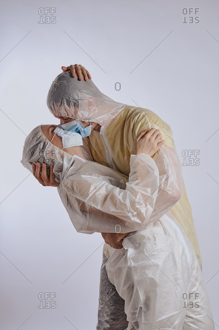 Couple embracing in full coverage protective coveralls