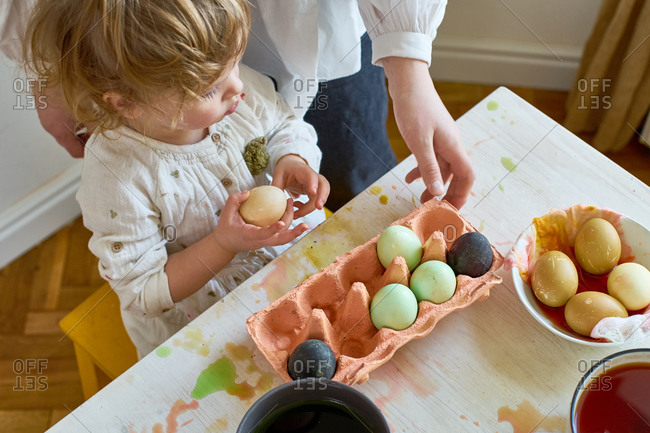 Overhead image of little girl dyeing eggs for Easter at home with her mother. Indoor spring activities. Natural dyes made from organic vegetables and spices