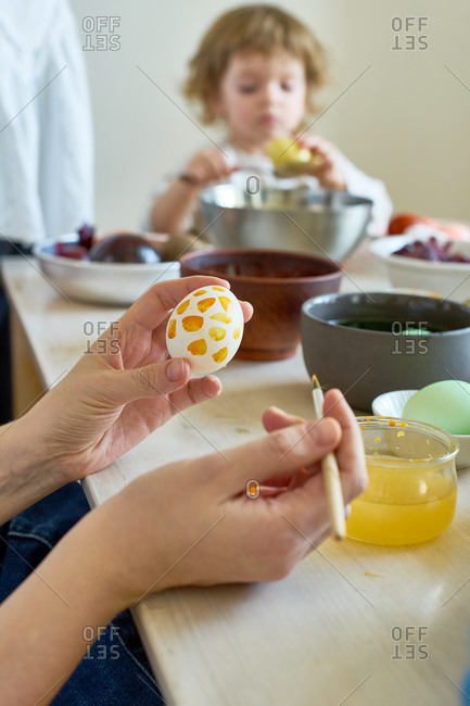 Little girl painting eggs for Easter at home with her mother. Indoor spring activities. Natural dyes made from organic vegetables and spices