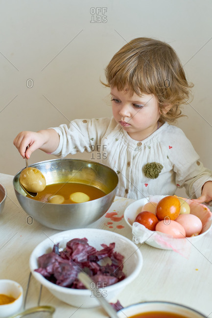 Little girl dyeing eggs for Easter at home with her mother. Indoor spring activities. Natural dyes made from organic vegetables and spices