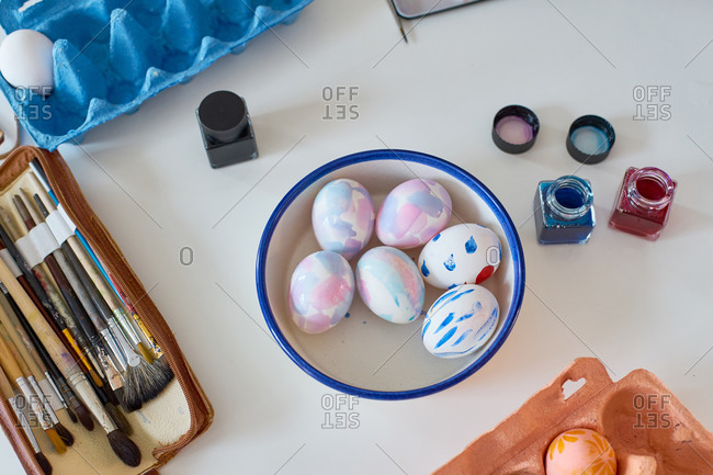 Little girl painting eggs for Easter at home with her mother using watercolor. Indoor spring activities