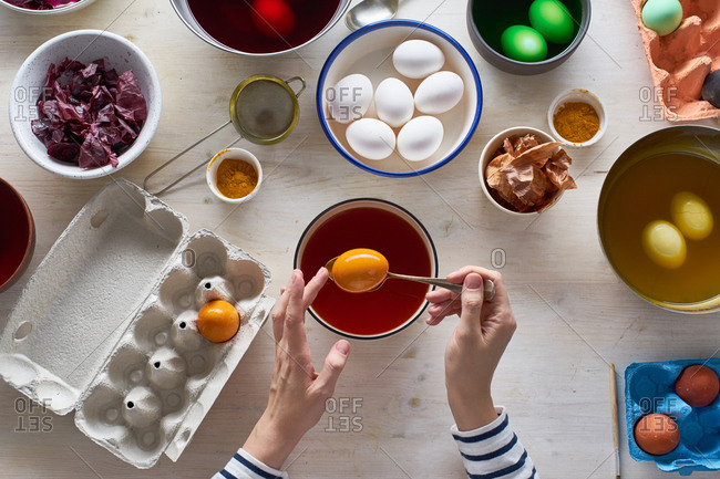 Female hands Easter eggs with natural dyes made from vegetables and spices