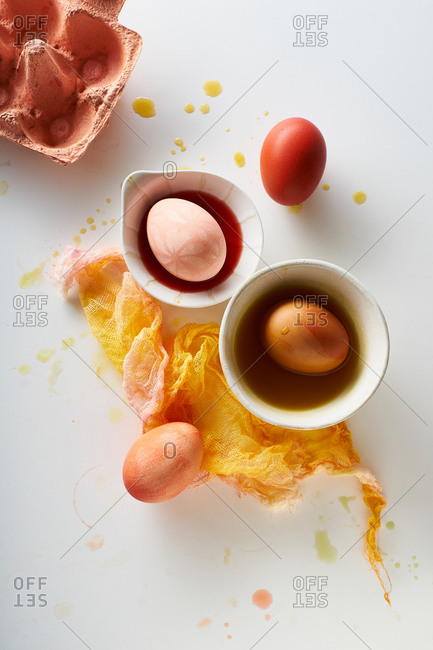 Top view image of colorful painted eggs in small white bowls on neutral background with negative space