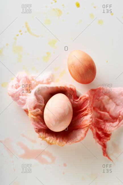 Top view image of colorful painted eggs and gauze clothes on neutral background with negative space