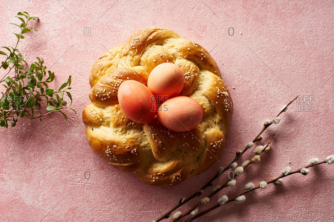 Overhead shot of traditional Easter bread - braided pastry with sesame seeds decorated with pink dyed eggs on pink background