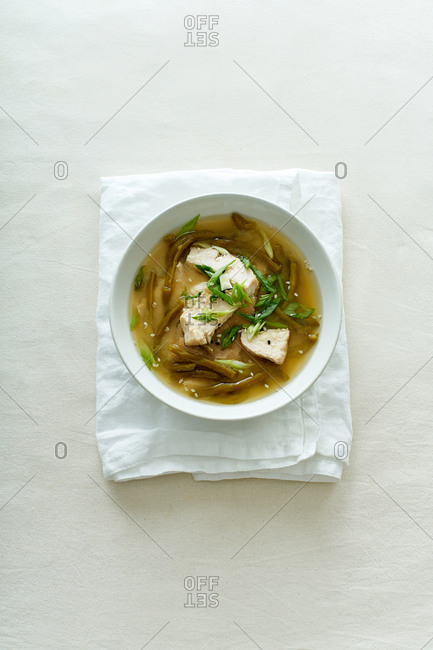 Miso soup with green beans and chicken on textile background