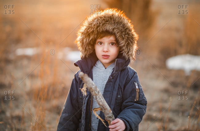 Portrait of little boy holding stick in golden haze as sun sets behind him