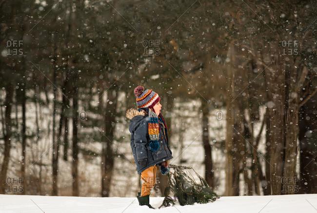 Little boy in winter gear standing in the snow