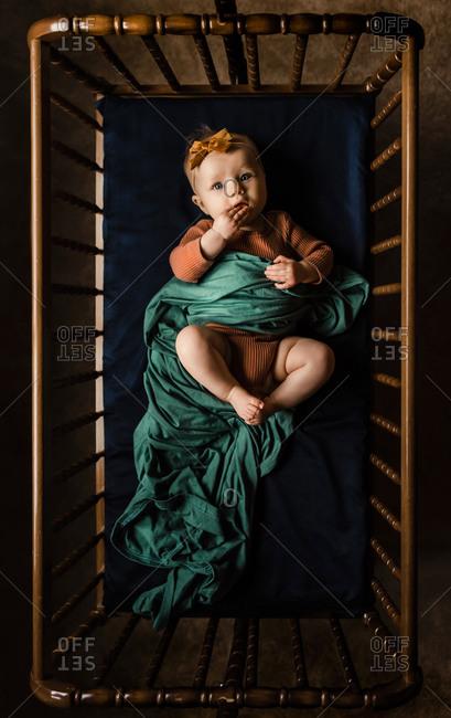 Overhead shot of baby girl lying in crib