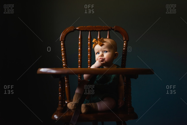 Little girl sitting in highchair looking at camera while sucking on fingers