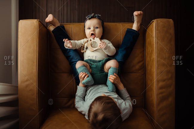 Overhead shot of baby girl laying in between big brother���s legs on chair, holding teether