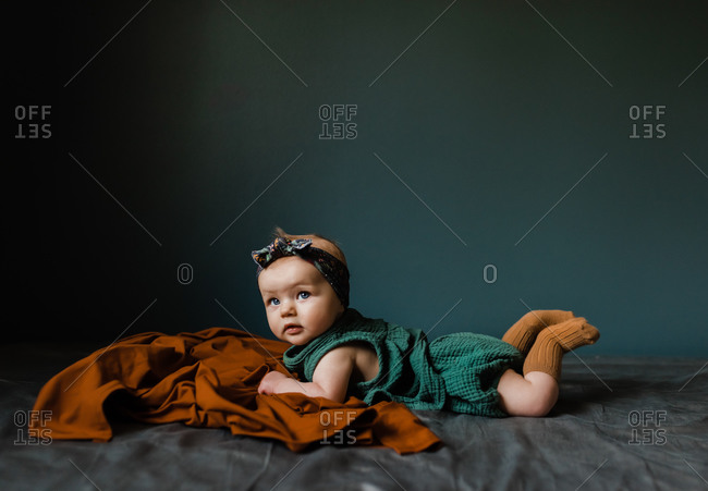 Little girl lying on bed doing tummy time