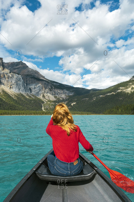 Redhead woman canoeing in clear turquoise water of Lake Louise in Banff National Park Canada
