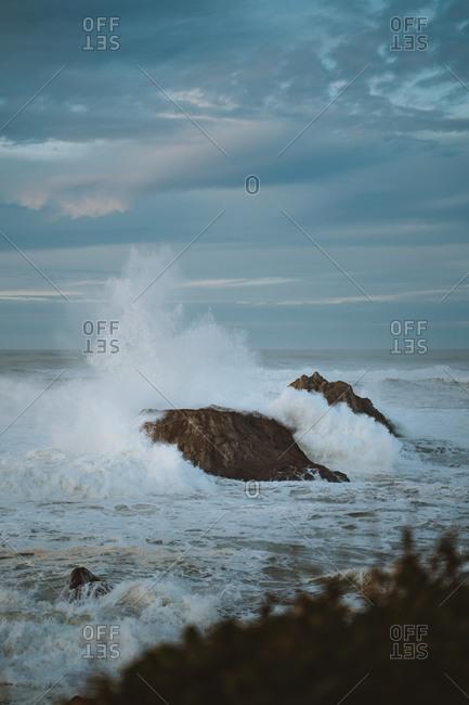 Big wave crashing against two big rocks on Biarritz coast