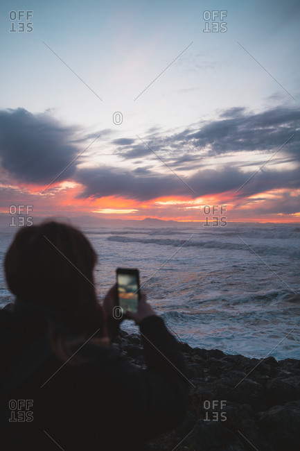 Girl taking a photo of the sunset on her smart phone