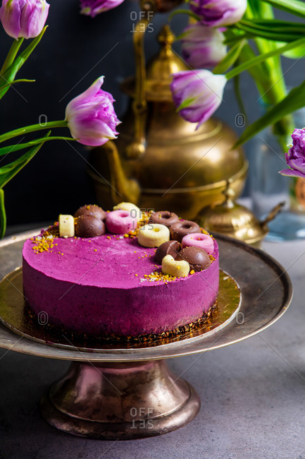Raw cake made of black currant, cashew, coconut oil and cocoa on a stand surrounded by tulips