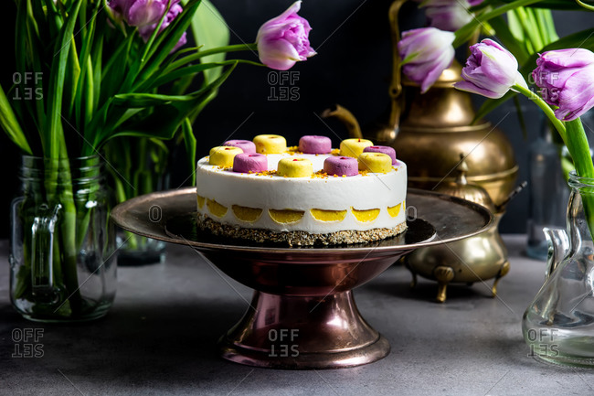 Raw cake made of mango, cashew, coconut oil , blueberries, dates on a stand surrounded by tulips