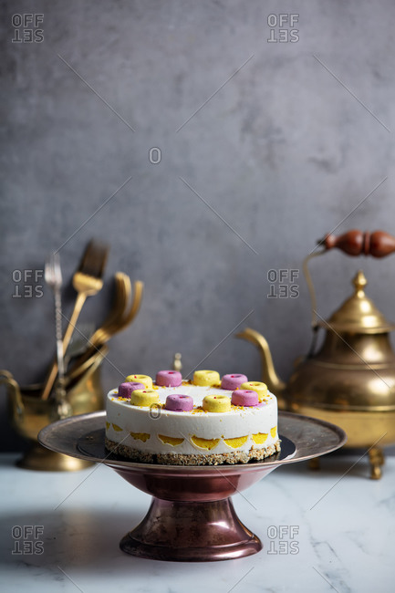 Raw cake made of mango, cashew, coconut oil , blueberries, dates on a stand surrounded by kitchenware