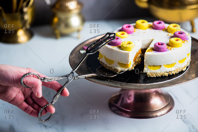 woman hand using cake tongs takes a piece raw cake made of mango, cashew, coconut oil, blueberries