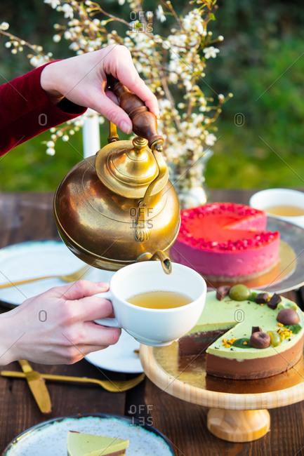 woman pours tea during a tea party in the garden