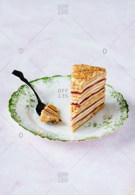 Russian Medovik cake on a green plate over pink backdrop