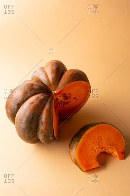 Orange pumpkin sliced on orange background