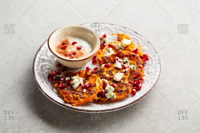 Pumpkin pancakes with cheese and cream on white plate