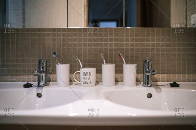 Straight shot of a double bathroom sink with toothbrush set.
