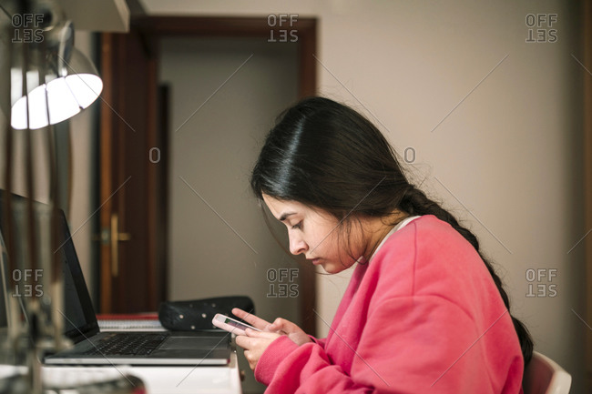 Teen girl studying with her mobile and laptop in her room