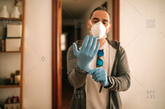 Young man with mask and gloves at home