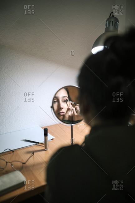 Teen girl putting on makeup in front of a mirror in her room