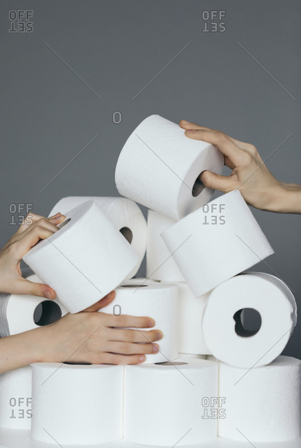 Hands grabbing at multiple rolls of toilet paper.