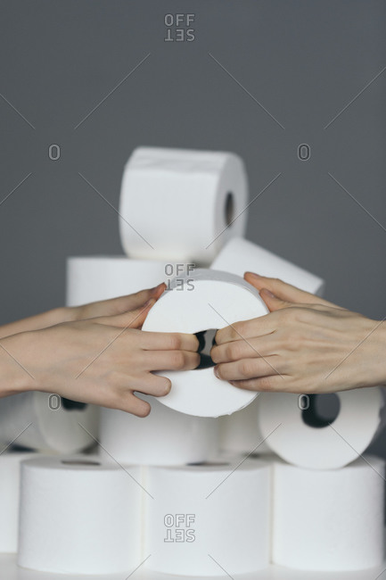 Two hands pulling on a roll of toilet paper with more toilet paper in the background
