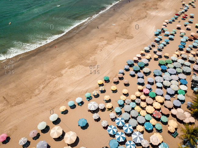 November 26, 2019: Aerial view of umbrellas on the shore of the beach in Kuta, Badung, Bali, Indonesia