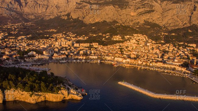 Aerial view of the sunset at the famous touristic city of Makarska in Dalmatia, Croatia. Famous Biokovo mountain is also visible.