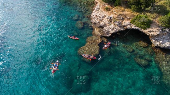Aerial view of kayakers exploring cave near Drvenik in Dalmatia, Croatia.